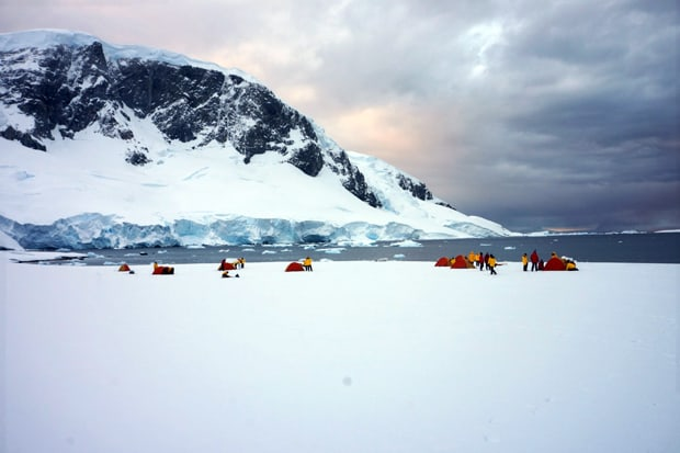 Guests camping on snow in Antarctica on an excursion from a small ship.