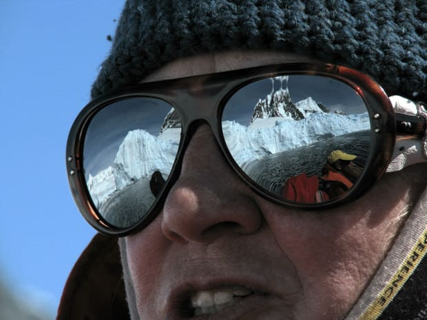 Close up of a small cruise ship crew member leading a skiff excursion in Antarctica wearing sunglasses reflecting the ice shelf and snowy peaks of Antarctica.