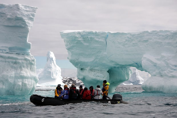 People on a zodiac inflatable raft in front of some Antarctic icebergs
