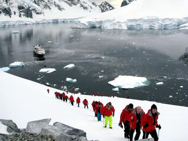 Group of guests on a hiking excursion on the snow in Antarctica with their small cruise ship in the background.