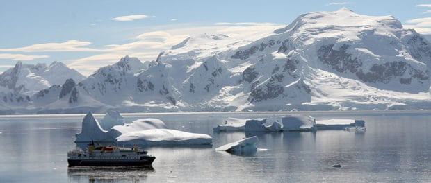 View of small expedition cruise ship in Antarctica surrounded by glaciers and snowy peaks.