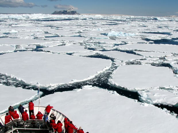 Guests on the bow of a small ship expedition cruise in Antarctica as the ship is breaking through the ice on the water.