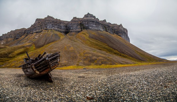 An old beached boat in the foreground with hills and cliffs in the background