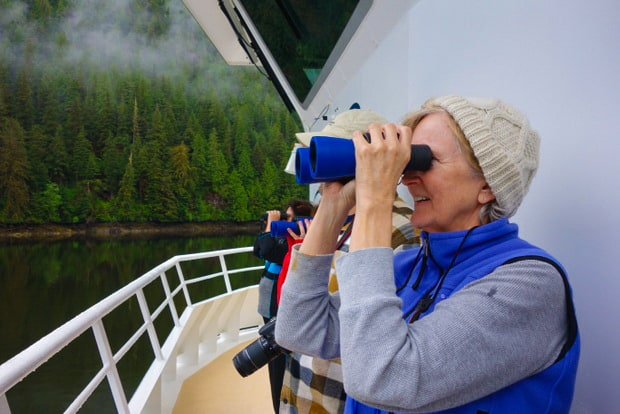 Guests aboard a small ship cruise in Alaska on deck looking for birds and wildlife with binoculars.