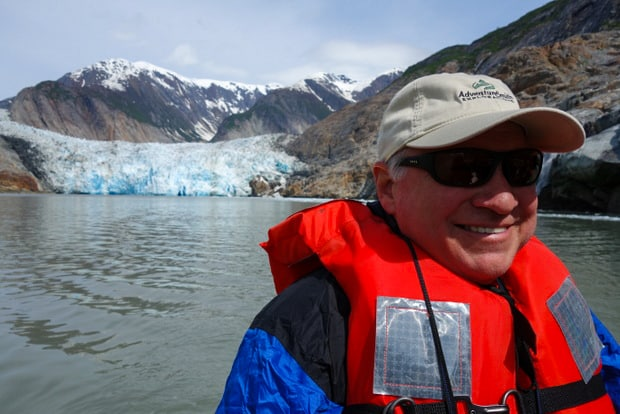 Guest aboard a small ship cruise in Alaska on an excursion kayaking in front of a glacier.