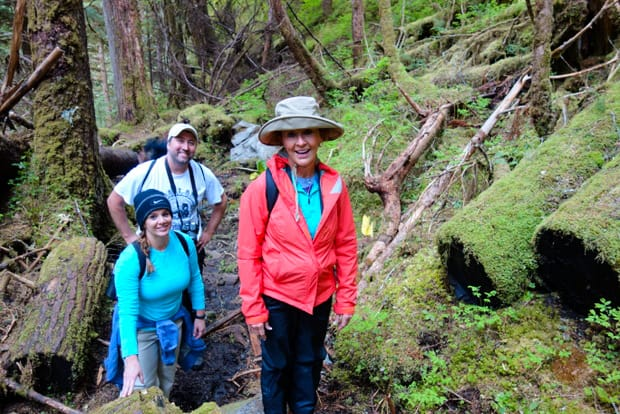 Guests on a small ship cruise in Alaska hiking through the forest on a land excursion.