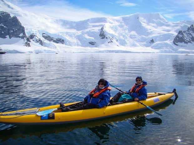 Small ship cruise expedition guests on a kayaking excursion in Antarctica.