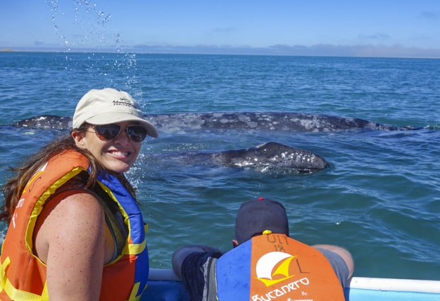 A woman traveler looking at the camera with a whale behind her surfacing in Baja.