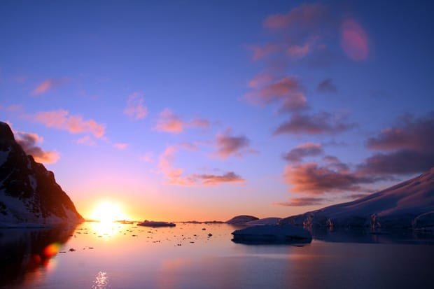 the sun setting on serene water in Antarctica