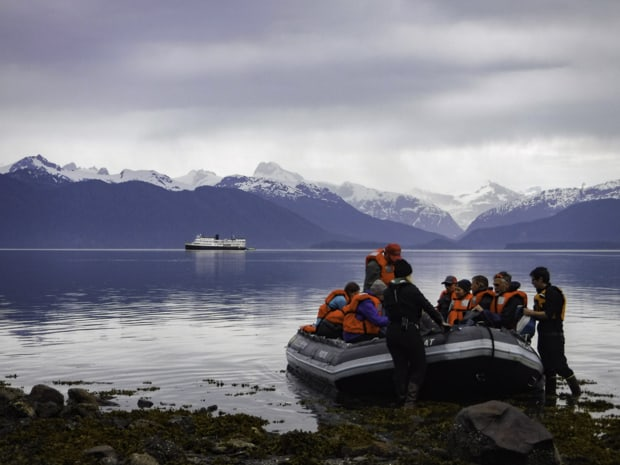 Alaskan travelers in a zodiac at shore with snow-capped mountains and Alaskan small ship cruise in the ocean.