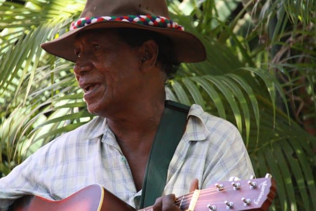 A man with a hat playing a guitar in Australia