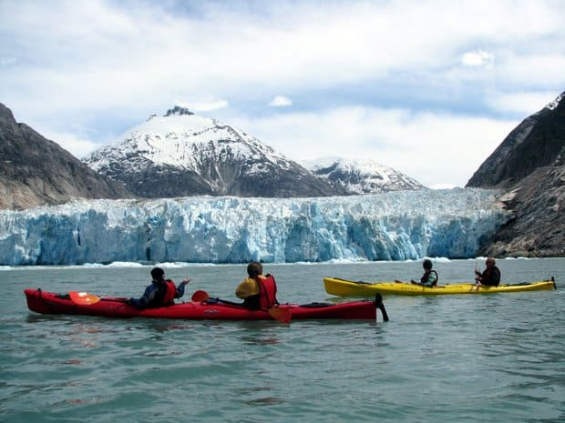 A group of people kayaking near a glacier in Alaska.