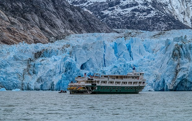 An Alaska small ship, the green and white painted wilderness discoverer floats in front of the teal jagged Dawes Glacier, as part of an Alaska cruise.