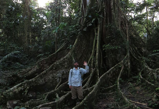 solo traveler standing in front of a tree's root system waving in the amazon