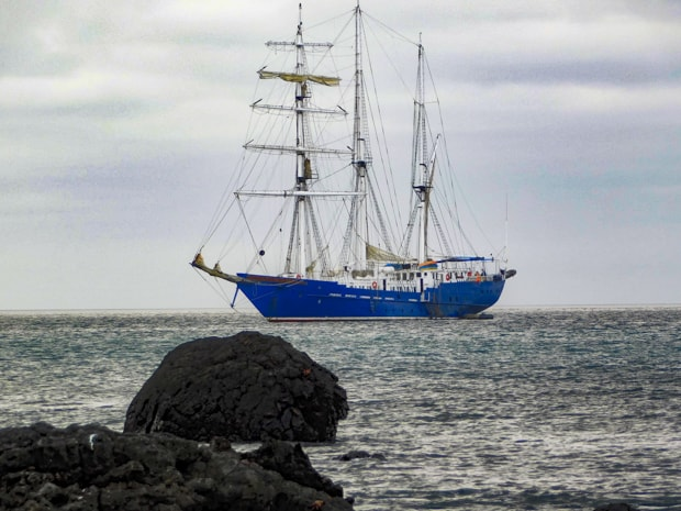 The small ship sailing ship S/S Mary Anne anchored in the ocean off the Galapagos Islands.