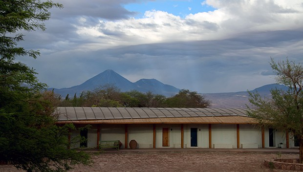 An images of the Explora Atacama lodge with a big volcano in the background.