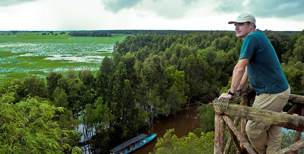 A man standing at the top of a canopy tower looking over the Amazon jungle.