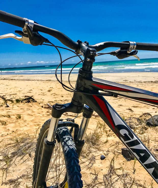 A mountain bike on a sandy beach with waves in the ocean on a sunny day.