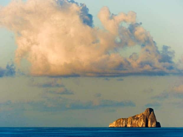 Large rock formation sticking out in the ocean.