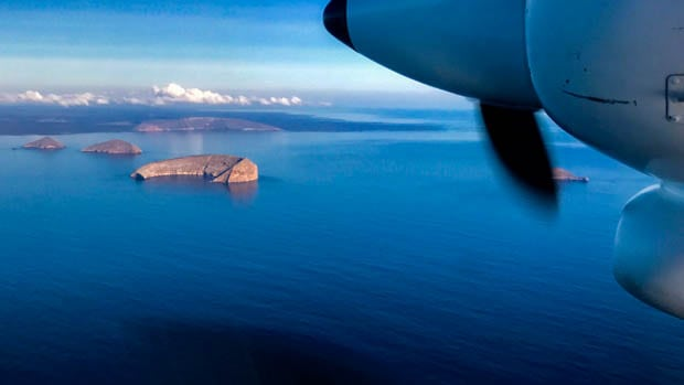View from a plane of the ocean and crescent shaped islands in the Galapagos.