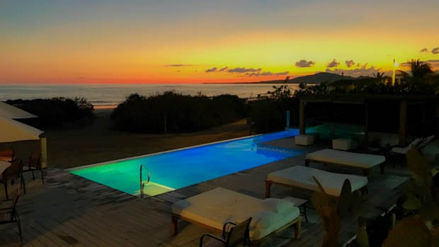 Yellow and orange sunset from a lodge with a pool and lounge chairs.
