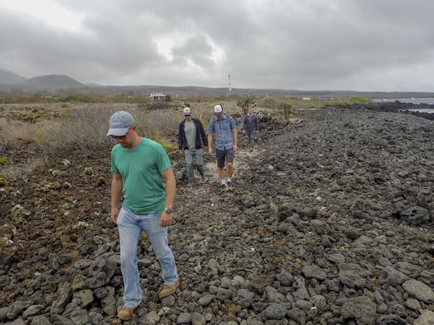 4 men walking on a rocky coastline on the Galapagos.