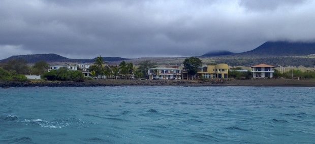 View from the ocean of the town of Floreana lined with colorful building along the rocky shoreline.