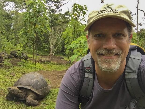 Galapagos traveler smiling with a land tortoise walking next to him on a Galapagos hike.