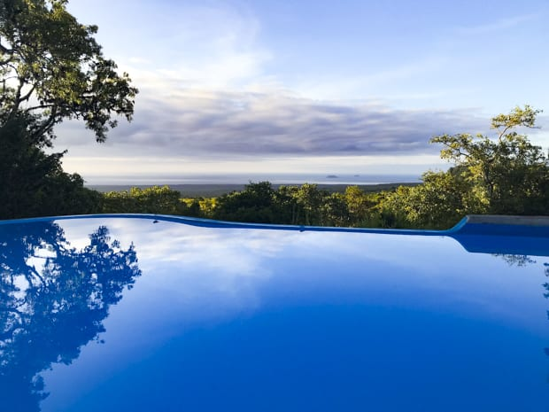 View of a blue pool overlooking scenic landscape on a Galapagos land tour.