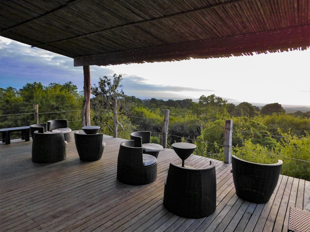 Thatched roof and deck with tables and chairs overlooking the landscape at the Galapagos Safari Camp.