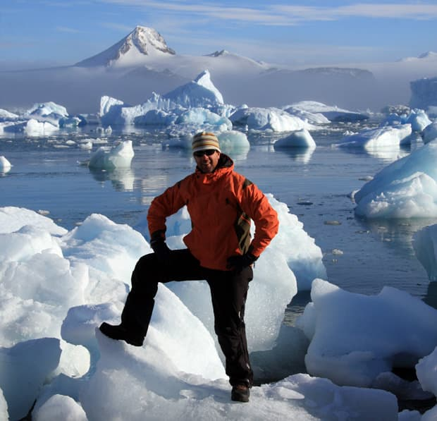 Guest aboard a small ship cruise in Antarctica posing with foot on top of an iceberg near shore with many icebergs in the background.