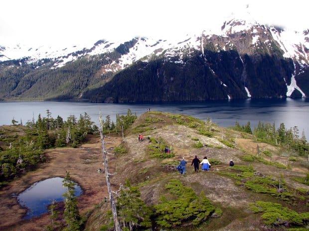 People hiking down a ridge in Alaska.