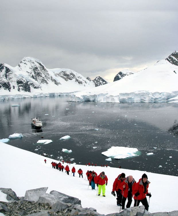 group of travelers on an Antarctica land tour with a small ship in the background