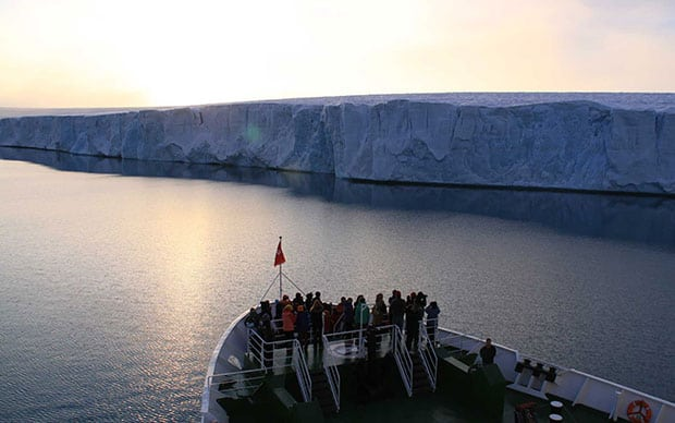 Travelers on a small expedition ship through the Arctic grouped up on the bow to watch the sunset with a large polar ice sheet to the right.