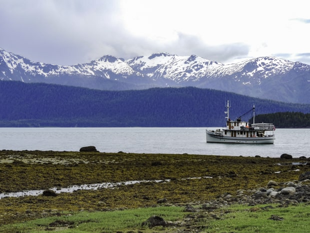A small ship cruise anchored in the water in Southeast Alaska among snow-capped mountains and rocky shore.