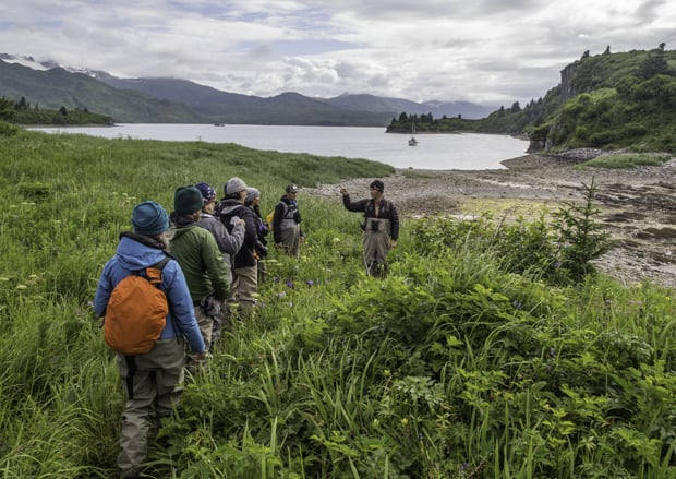 Group of Alaskan travelers hiking near a rocky shore with guides giving interpretation.