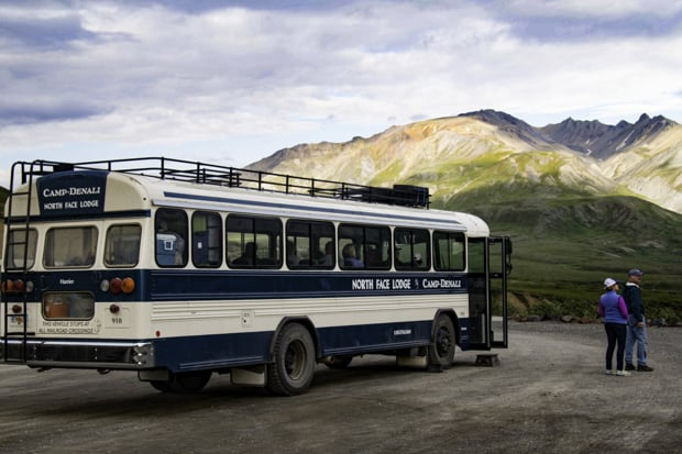 Two travelers visiting Denali National Park stand beside their Camp Denali private tour bus with mountains behind them.