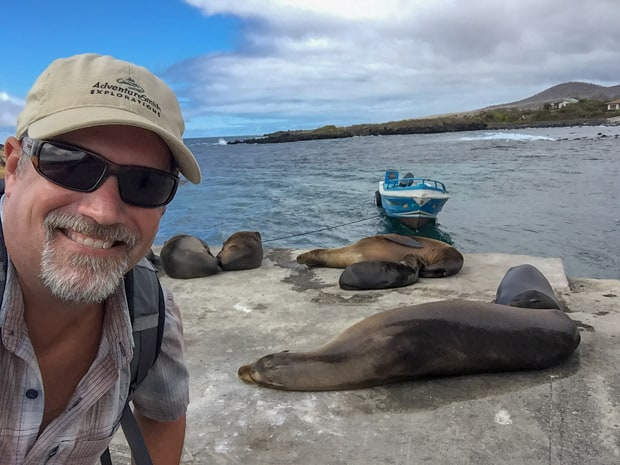 Galapagos traveler posing next to 5 sleeping sea lions with a small blue boat anchored in the water.