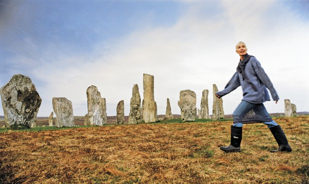 A solo female traveler with short gray hair walks among the Stones of Callanish in Scotland in tall boots and a scarf