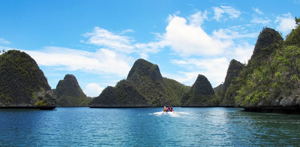 green karst islets in Indonesia with a zodiac cruising among them