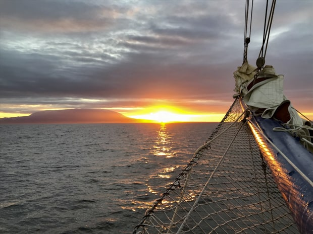 Tip of the narrow bow with net sailing on the ocean with the sunset.
