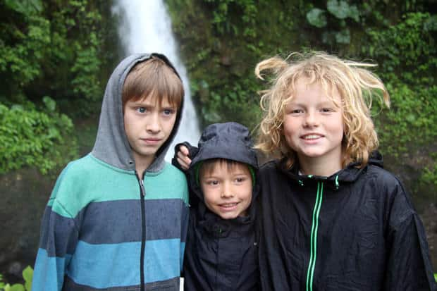 Children in front of a waterfall.