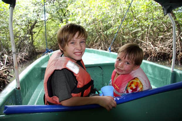 Children on an excursion from their small ship cruise getting up close to the forest on a skiff.