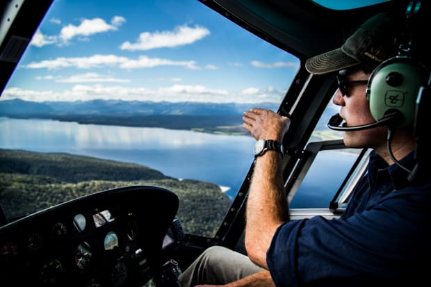 View from a helicopter above the waterways in New Zealand with a pilot pointing out sites.