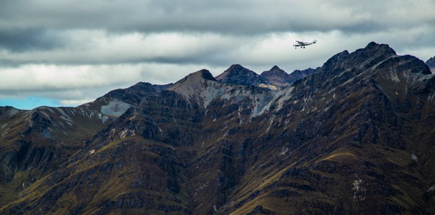 Plane flying aboard the peaks of a mountain in New Zealand seen from a small ship cruise.