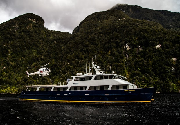Helicopter above a small ship cruise in the fjords in New Zealand.