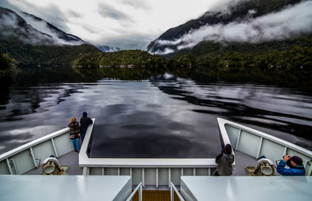 View from the stern of a small ship cruise going through misty fjords in New Zealand.