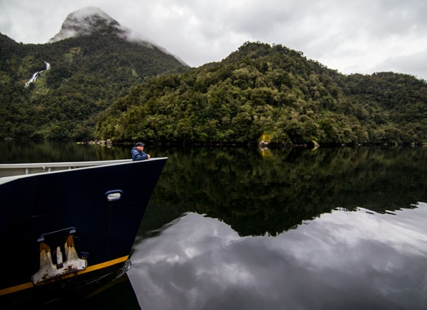 Man standing alone at the bow of a small ship cruising through the fjords of new zealand.