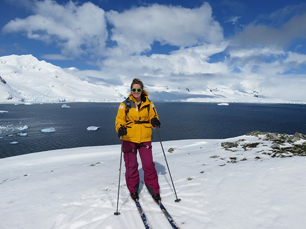 Girl smiling in yellow jacket cross country skiing in Antarctica after reaching 7 continents