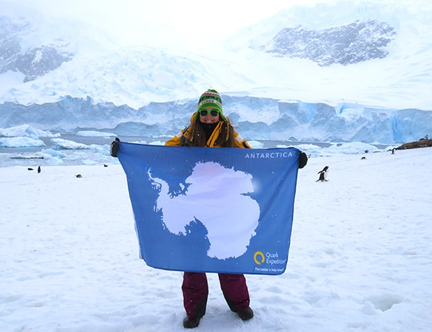 Happy guest celebrating 7 continents holding an Antarctica flag while standing on land with penguins behind her